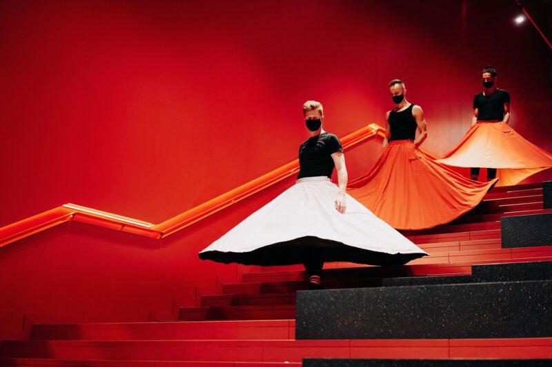 Renginio fotografija, kurioje vaizduojami trys žmonės, vilkintys plačiais sijonais.