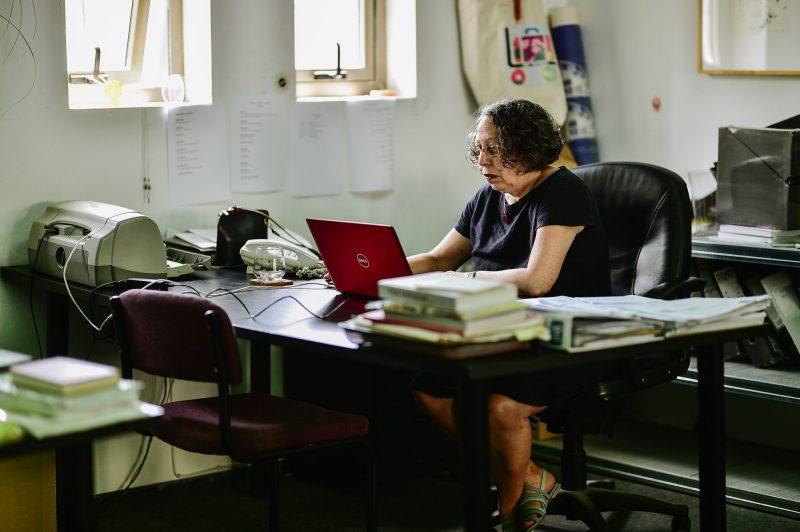 Kūrinio reprodukcija, kurioje vaizduojama prie kompiuterio sėdinti moteris